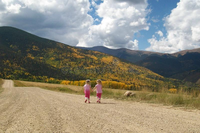 Little Girls Twin Sisters Friends Walking Hand in Hand. royalty free stock photo