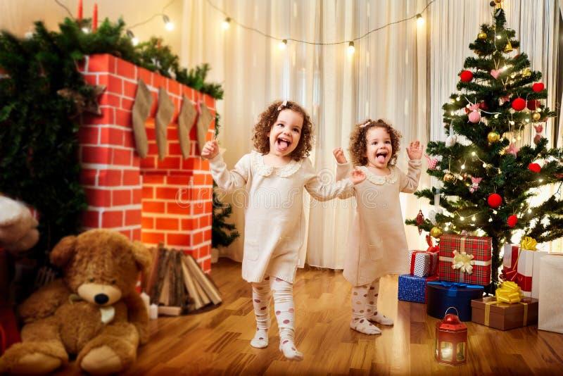 Little girls twins children Christmas dancing, having fun, laugh royalty free stock images