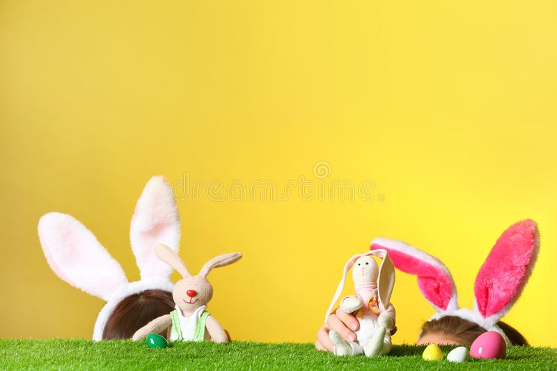 Little girls wearing rabbit ears headbands and playing with toy Easter bunnies on green grass surface stock photo