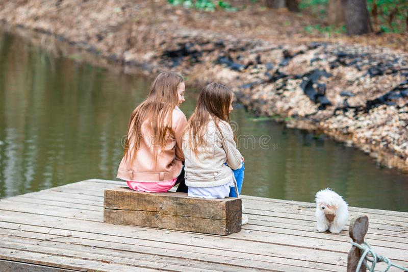 Little girls with a white puppy. A puppy in the hands of a girls. Little kids sitting together with puppy on the lake stock photography