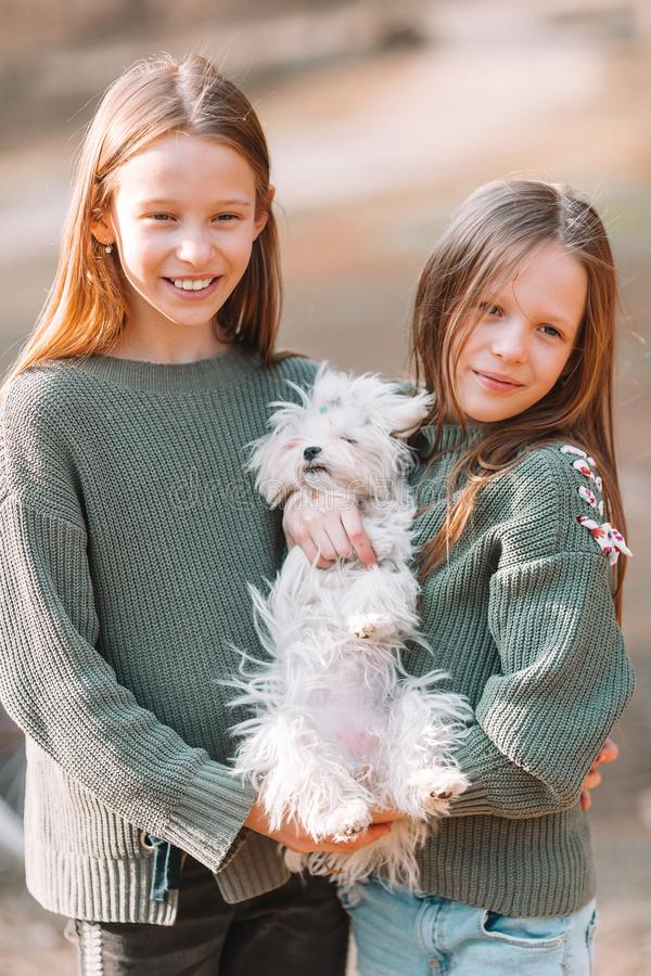 Little girls with a white puppy. A puppy in the hands of a girls. Little smiling girls playing and hugging puppy in the park stock photography