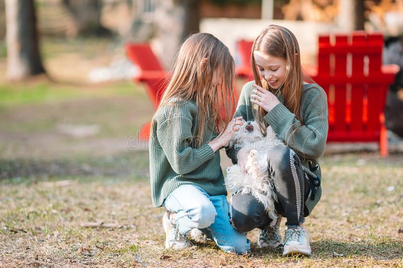Little girls with a white puppy. A puppy in the hands of a girls. Little smiling girls playing and hugging puppy in the park royalty free stock photo