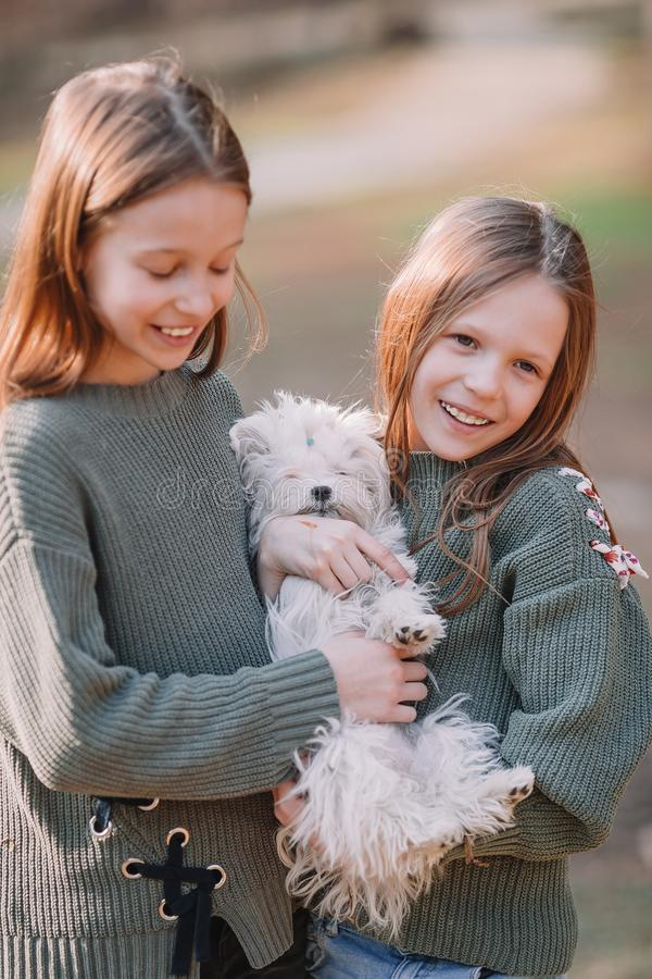 Little girls with a white puppy. A puppy in the hands of a girls. Little smiling girls playing and hugging puppy in the park royalty free stock photography