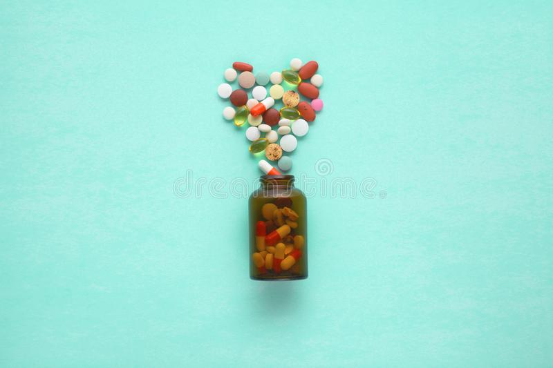 Little glass bottle with pills spilled over a table stock photos