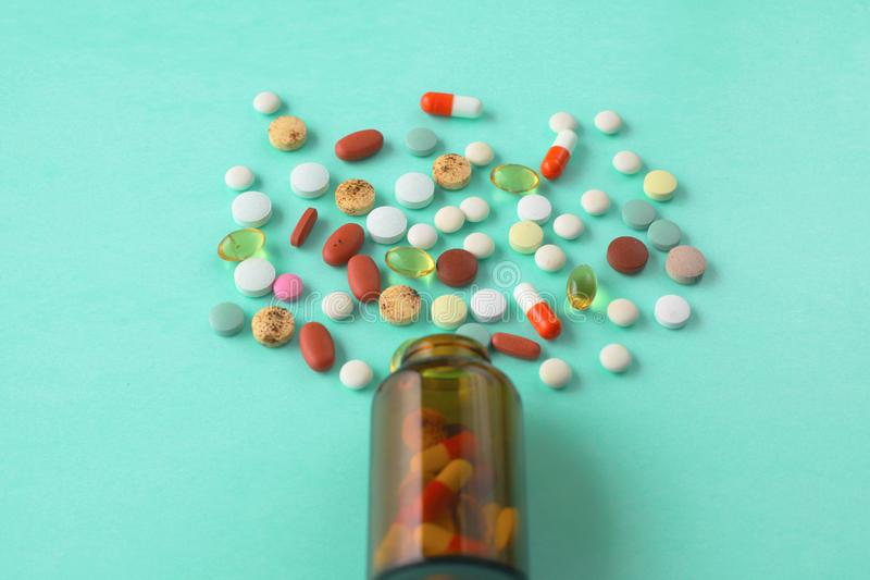 Little glass bottle with pills spilled over a table stock image