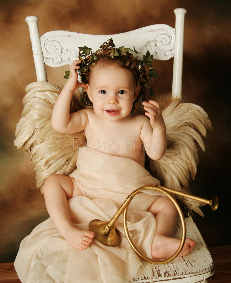 Little Gold and brown angel child with a gold horn. Portrait of a beautiful young girl dressed up as an angel with brown wings and a gold dress, wearing an ivy stock photos