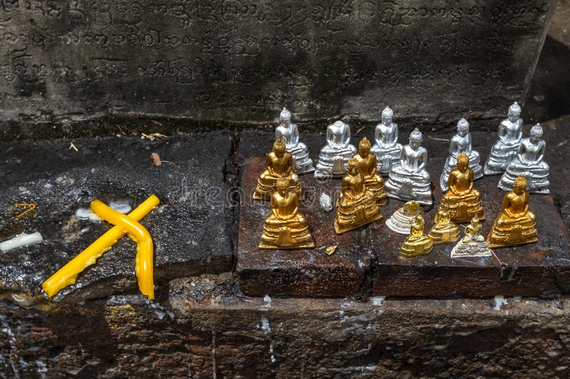 Little gold and silver buddha figurines with two yellow candles stock photography