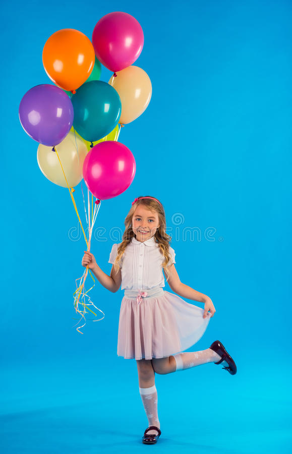Little good girl. Portrait of a little girl with balloons isolated on blue background stock photo
