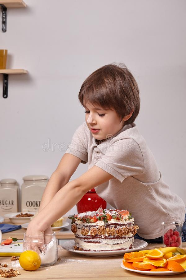 Little boy is making a homemade cake with an easy recipe at kitchen against a white wall with shelves on it. Little good-looking boy with smeared in powdered royalty free stock photo