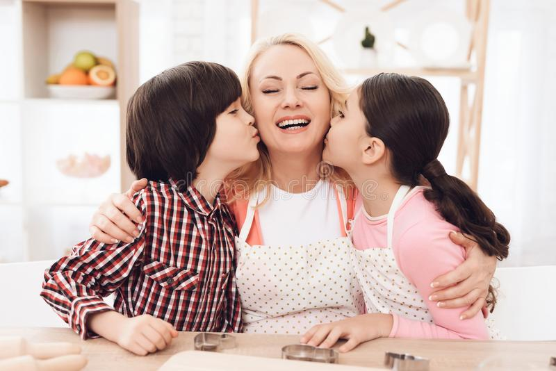 Little grandchildren kiss beautiful grandmother sitting in kitchen. Baking cookies. royalty free stock images