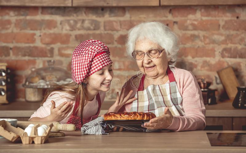Little granddaughter with granny enjoying homemade fruit pie. Little granddaughter with her senior granny enjoying the smell of hot homemade fruit pie stock images