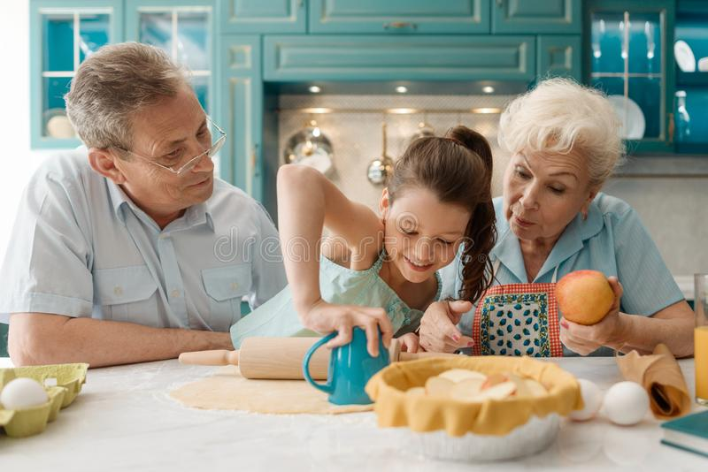 Little granddaughter making cookies. Cutting them out with a cup. Cooking with grandparents royalty free stock photos