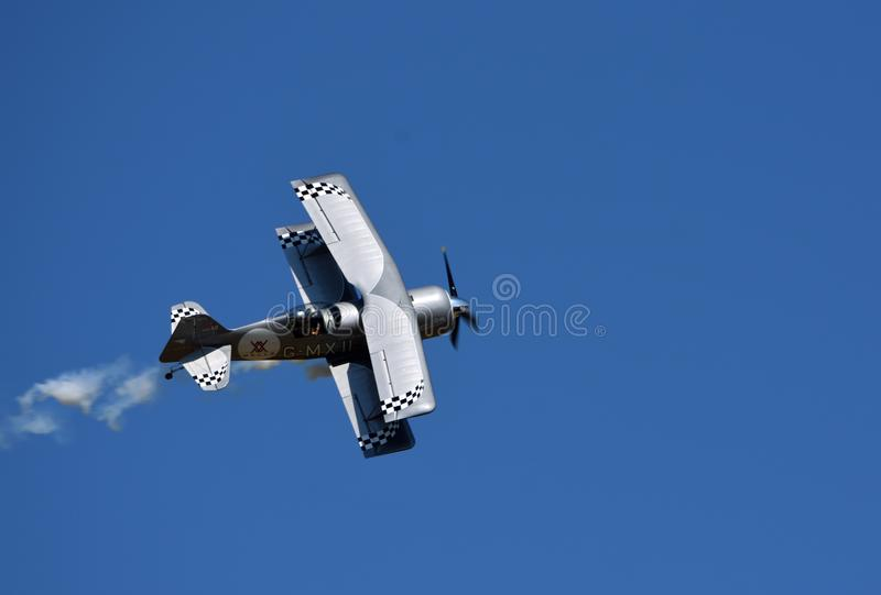 Pitts Model 12  stunt byplane  with smoke trail and blue sky. royalty free stock photos