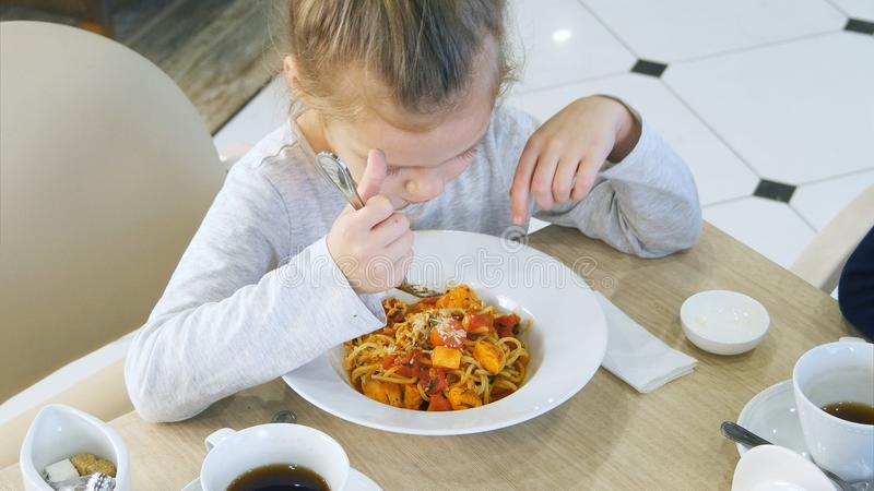 Little grimy girl eating careless her pasta in cafe. stock image