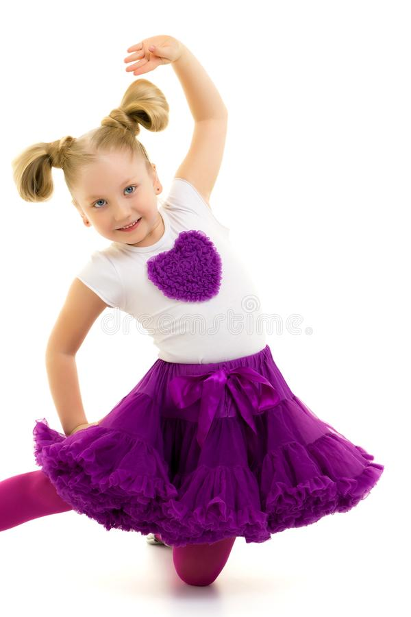 The little gymnast perform an acrobatic element on the floor. stock images