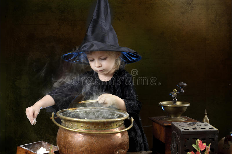 Little halloween witch with cauldron royalty free stock photography