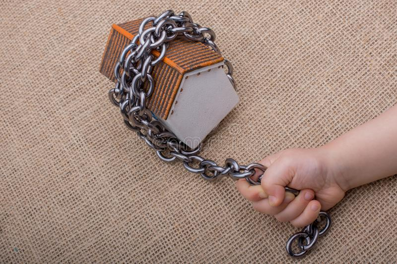 Little hand holding a chain around  a model house. On a brown background stock photography