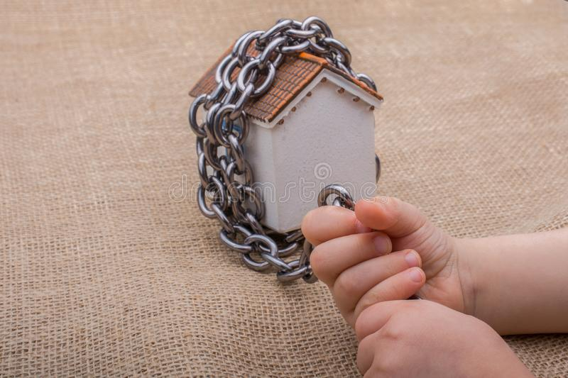 Little hand holding a chain around  a model house. On a brown background royalty free stock images