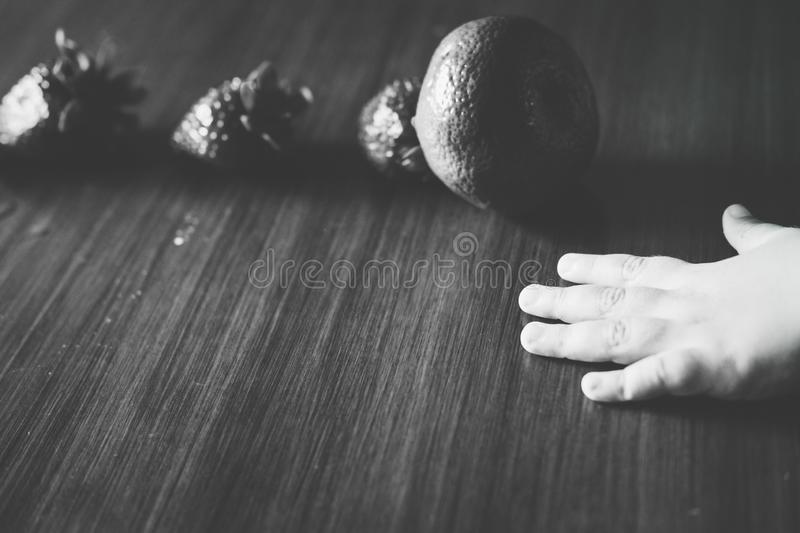 Little hand near a fruit line formed by three strawberries and a tangerine royalty free stock images