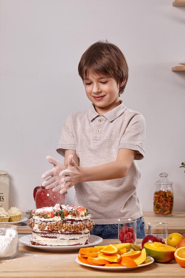 Little boy is making a homemade cake with an easy recipe at kitchen against a white wall with shelves on it. Little handsome boy with smeared in powdered sugar royalty free stock image
