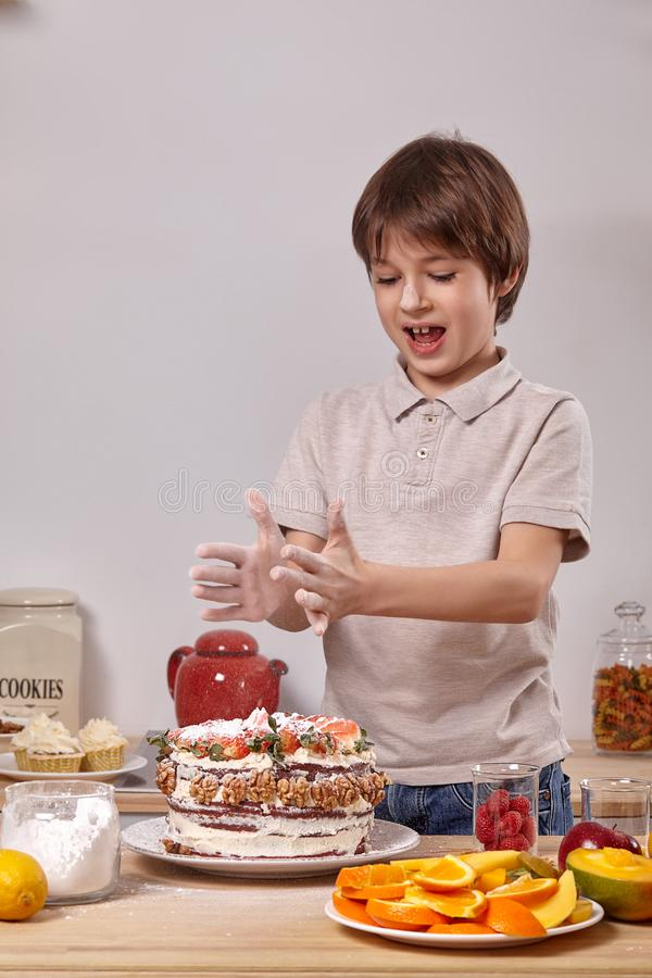 Little boy is making a homemade cake with an easy recipe at kitchen against a white wall with shelves on it. Little handsome child with smeared in powdered royalty free stock images