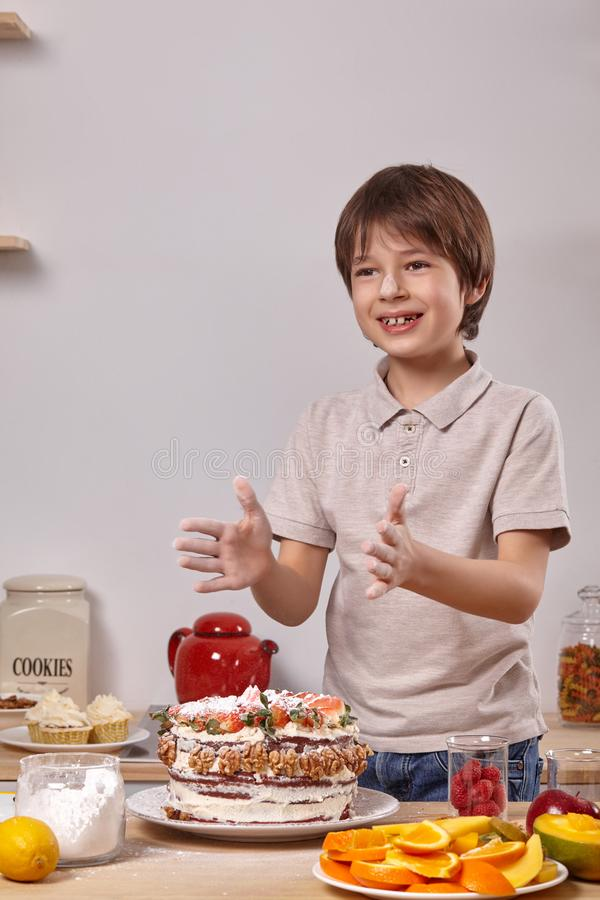 Little boy is making a homemade cake with an easy recipe at kitchen against a white wall with shelves on it. Little handsome kid with smeared in powdered sugar stock image