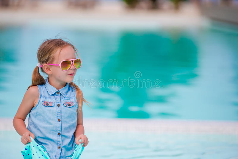 Little happy adorable girl on the edge of outdoor pool stock photos