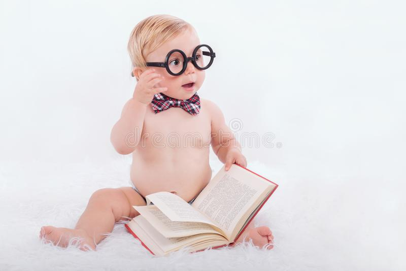 Little happy baby reading a book stock image