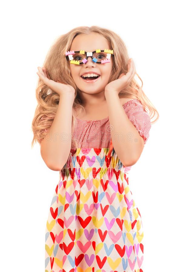 Little happy blonde girl in dress with hearts and glasses looks up side opening mouth in surprise royalty free stock image