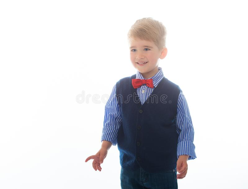 Little happy boy. Little boy in blue vest with red bow tie isolated on white background stock image