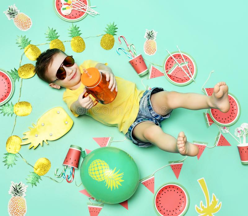 Little happy boy celebrate picnic party lying on a floor in yellow t-shirt and sunglasses happy smiling with pineapple. Little happy boy celebrate picnic party stock photo