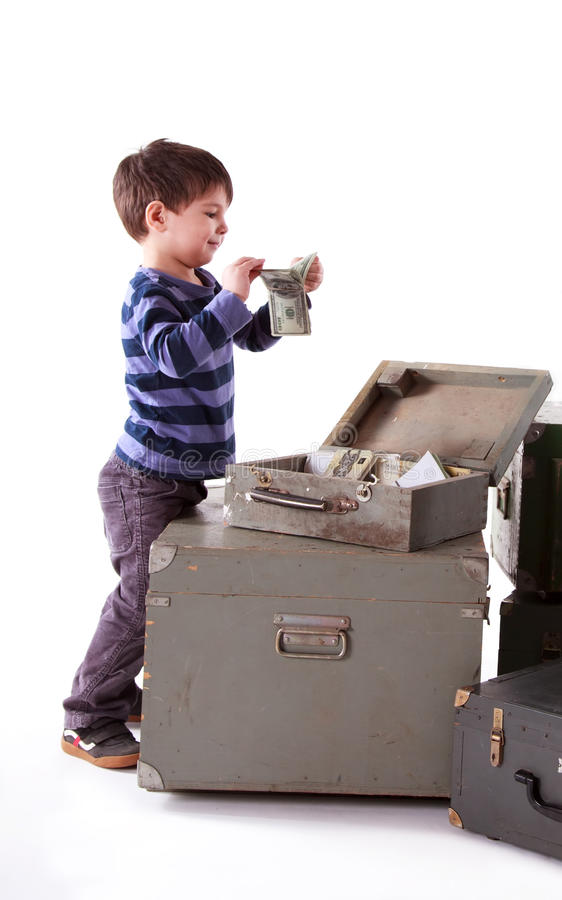 Little happy boy found the money in an old suitcase. Little happy boy found the money in an old wooden suitcase stock photography