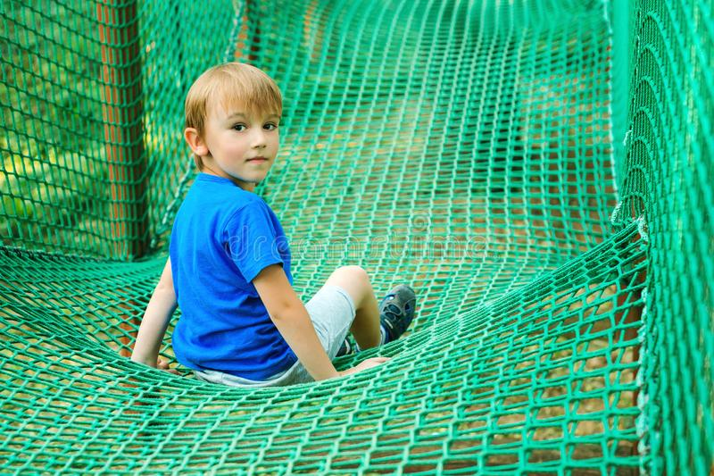 Little happy boy having fun in adventure park. Child playing at outdoors playground. Happy childhood. Summer holidays. Kid plays stock photos