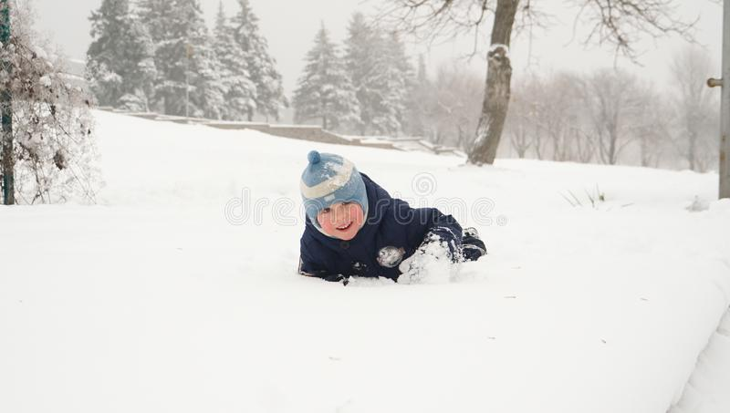 Little boy having fun floundering in the snow in winter park royalty free stock images