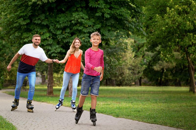 Little happy boy and his parents roller skating stock photo