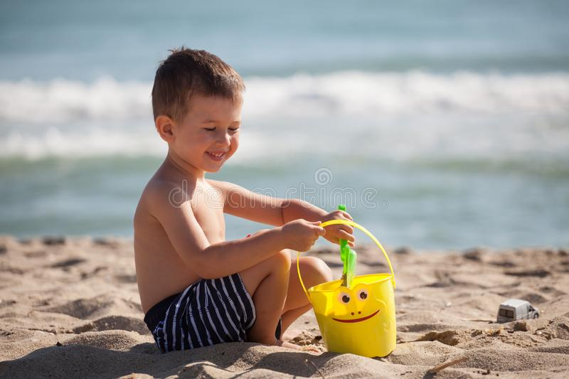 Little happy boy play with sand and toys on summer beach stock images