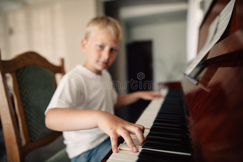 Little happy boy plays piano stock photo