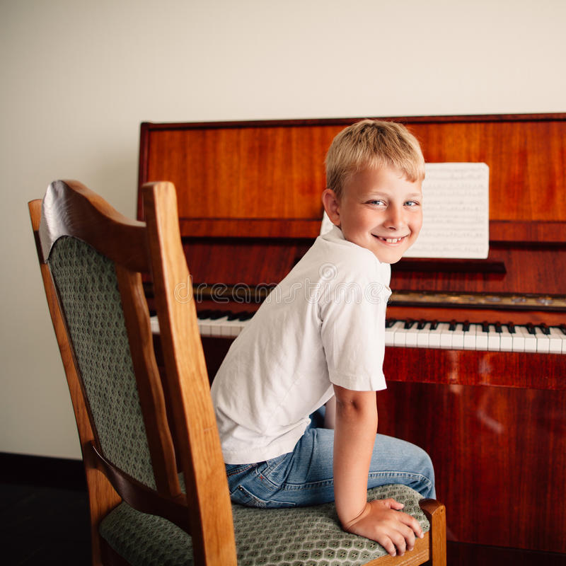 Little happy boy plays piano royalty free stock photo