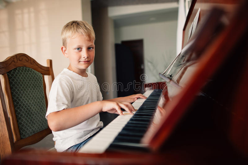 Little happy boy plays piano royalty free stock image
