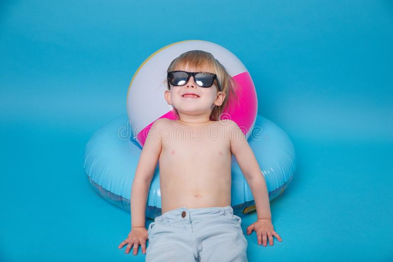 Little happy boy in sunglasses with big inflatable ball on blue background stock image