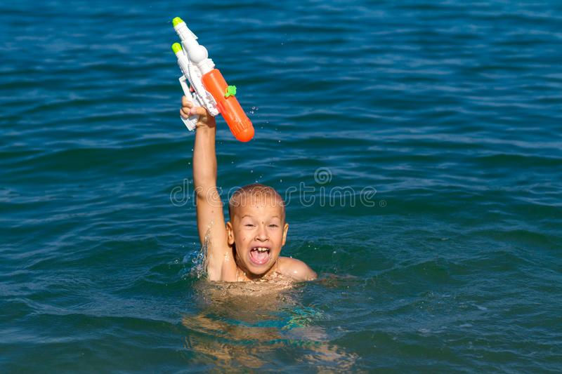 Little happy boy swimming in the sea with water gun concept happy childhood royalty free stock photos