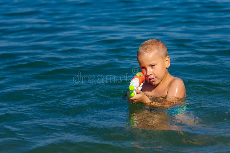 Little happy boy swimming in the sea with water gun concept happy childhood royalty free stock photography