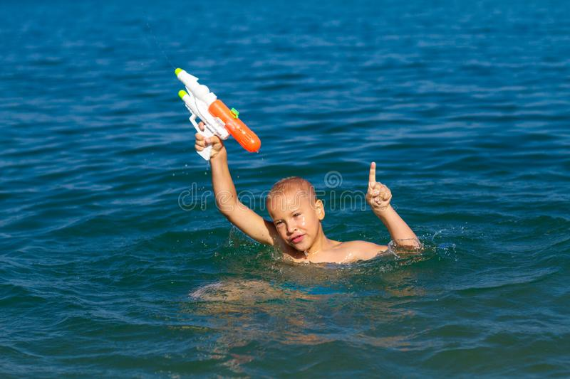 Little happy boy swimming in the sea with water gun concept happy childhood stock photography