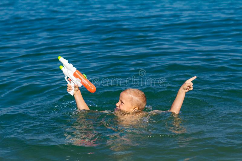 Little happy boy swimming in the sea with water gun concept happy childhood royalty free stock images