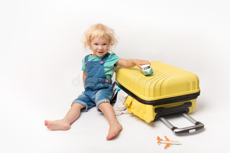 Little Happy Caucasian curly girl in comfortable denim clothes child sitting on yellow suitcase. tourist in shirt with plain And stock image