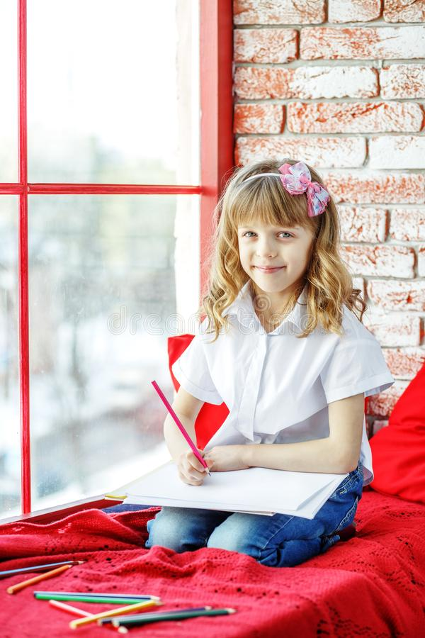 Little happy child sitting on the window sill and drawing. The c royalty free stock images