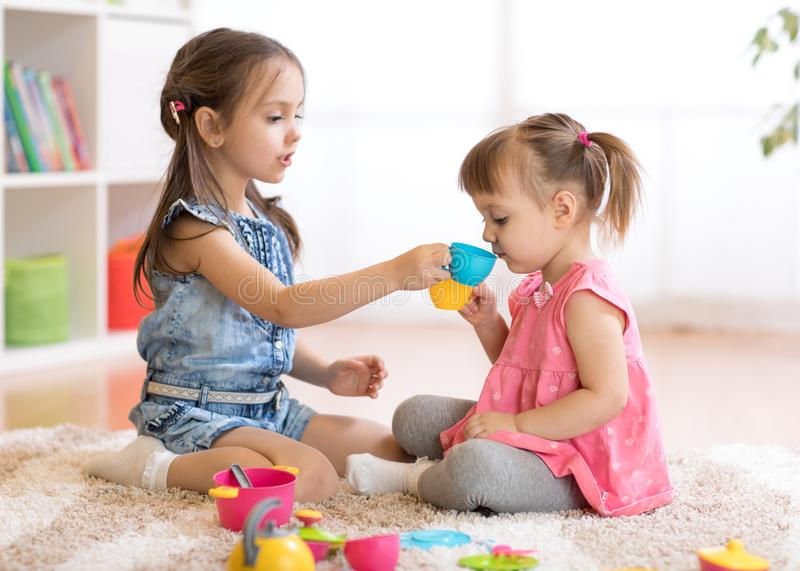 Little happy children, cute toddler and kid girls play with plastic toy kitchen on floor at home or kindergarten royalty free stock photo