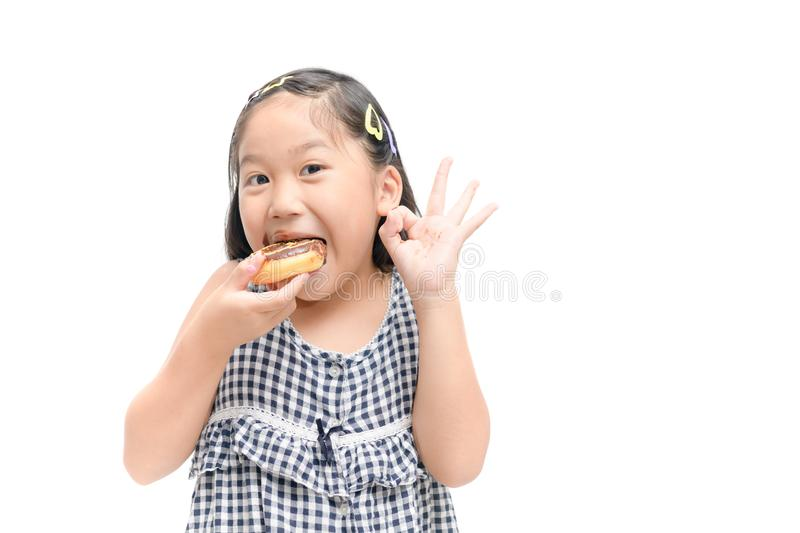 Little happy cute girl is eating donut isolated stock photo