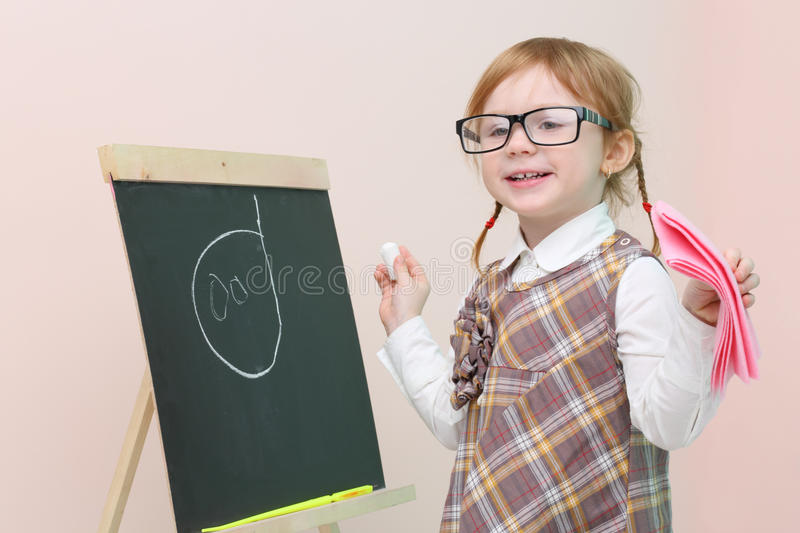 Little happy girl in glasses with pink rag chalk draws face stock photos