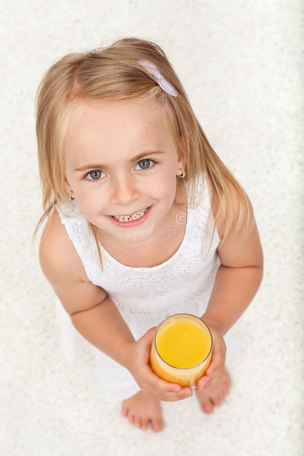 Little happy girl having a glass of fruit juice - top view stock photography